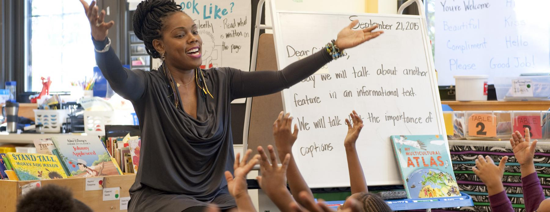 An elementary school teacher extends her arms into the air as she leads her students in song