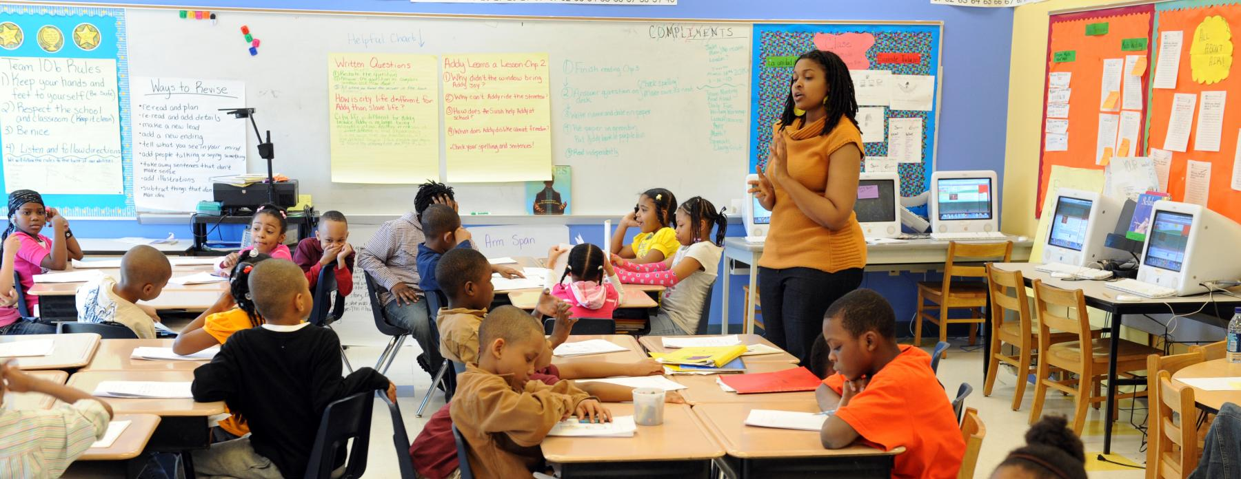 A teacher leads a class of elementary school students